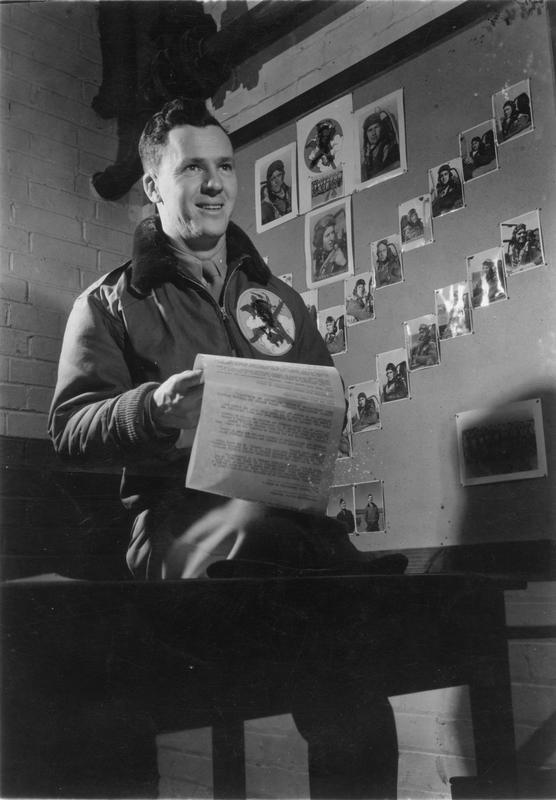 Lieutenant Colonel John A. Brooks of the 2nd Scouting Force at a briefing, 11 April 1945. Passed as censored 11 Apr 1945. Handwritten caption on reverse: '355FG/2 Scout Force.' Printed caption on reverse: 'USSTAF Foto By Sgt. Eugene L. Kammerman, #12. Good news about bombs on the targets - and the parts the Scouting Forces played in the success, comes over the teletype from division headquarters and is read to the scouting pilots by Lt. Col. John A. Brooks, of Chicago, Ill., commanding officer of a scouting force and a former B-24 Liberator lead pilot of 30 bomber missions. Col. Brooks holds the Distinguished Flying Cross, and the Air Medal with five clusters.' On reverse: SHAEF Field Press Censor [Stamp].