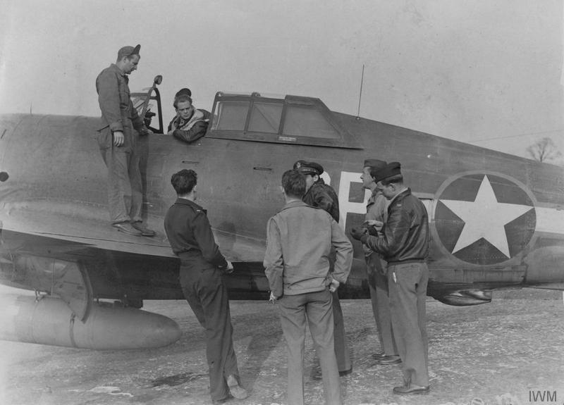Personnel talk to Lieutenant-Colonel Oscar Coen of the 334th Fighter Squadron, 4th Fighter Groupin the cockpit of his P-47 Thunderbolt after a mission over Paris, 15 October 1943. Printed caption on reverse: 'American Thunderbolt fighters are proving a terror to the German pilots (former members of the R.A.F.). Flying their high altitude fast diving fighters, that have accounted for many enemy planes. In the raid over Paris the fighters of this station accounted for 17 down, 5 probables and one damaged. 15/10/43.' Printed damaged caption on reverse: 'O.P.S. Lt. Col. Oscar Coen of Illinois is an Ace and one of [the...] original Eagle Squadron. He has won both the British and Ameri[can...] D.F.C. He is here seen seated in his plane with fellow pilot[s...] around him.' On reverse: Daily Sketch [Stamp].