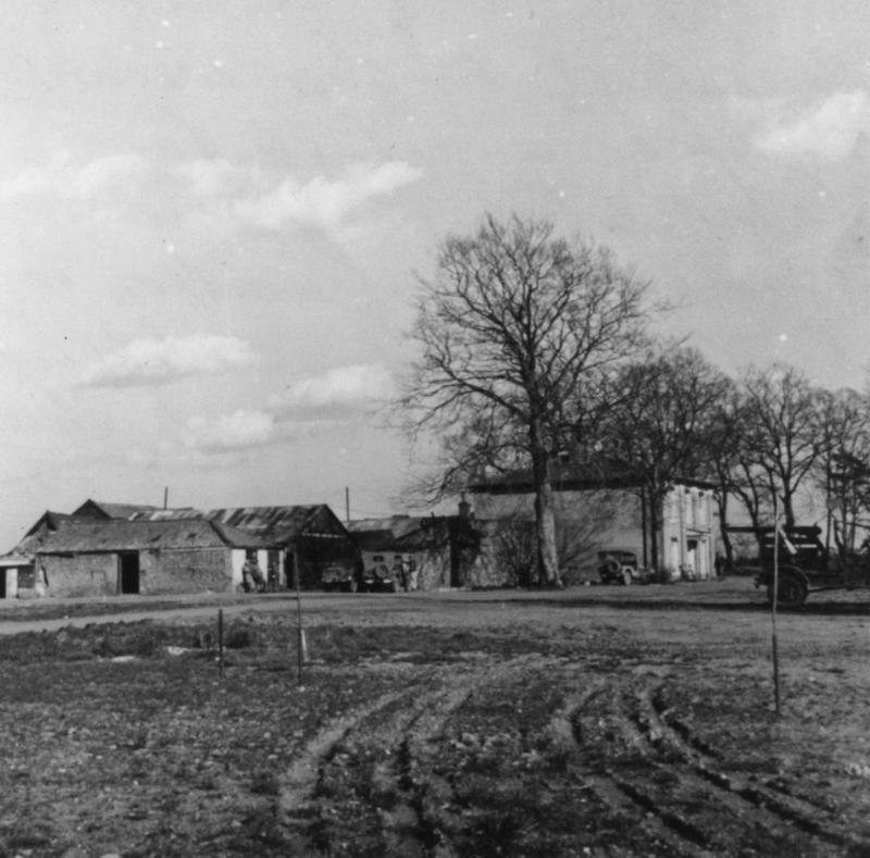 A farm house used by Lieutenant Colonel David C Schilling of the 56th Fighter Group at Halesworth. Handwritten caption on reverse: 'This farm house at Halesworth Air Base used the space available for Dave C. Schilling and his 62nd Fighter Squadron to have their admin, Intelligence, Operations, Engineering, Armament and Communications. A hardstand just in front of the main house ran off the runway, in three days with the help of the 33rd Service Group. Carpenters and everyone in holding a faint hush - the