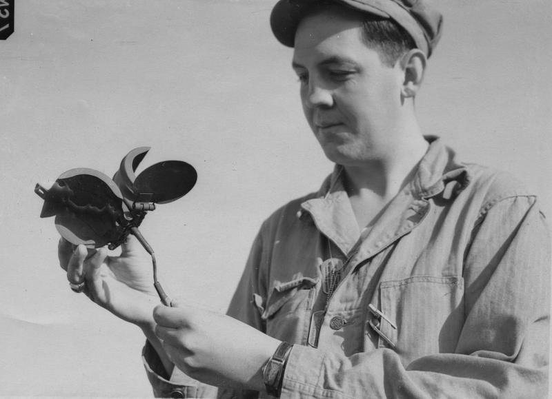 Corporal George J. Oelkers of the 390th Bomb Group, examines a German butterfly bomb, dropped on Parham. Originally passed for publication 23 Aug 1943, but then revoked from publication same day. Printed caption on reverse: 'U.S. Bomber Station Raided Last Night. Associated Press Photo Shows:- Cpl. George J. Oelkers, of Maple Wood, N.J., holding up the outer casing of one of the butterfly bombs. WOR 259912. 23-8-43-Y.' On reverse: Associated Press, US Army Press Censor ETO, US Army General Section Press & Censorship Bureau and Ministry of Information [Stamps].