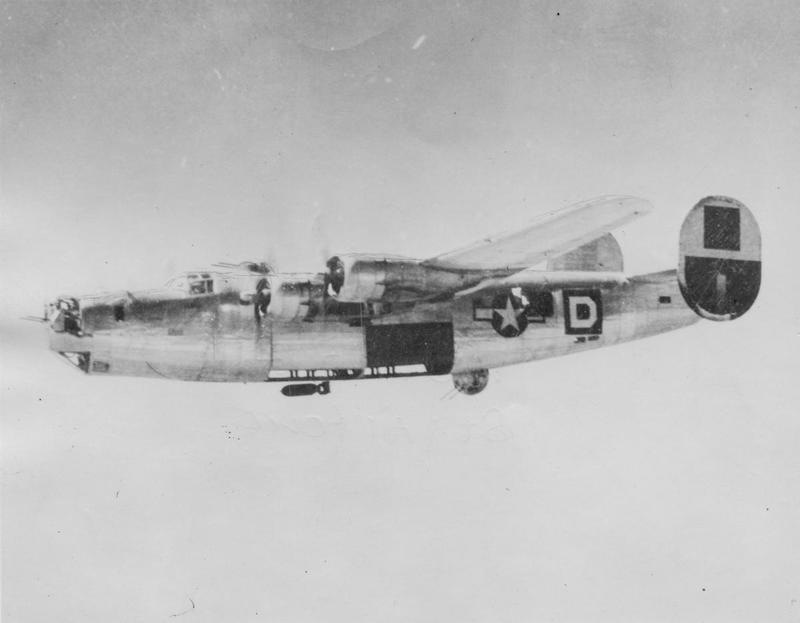 A B-24 Liberator of the 464th Bomb Group, 15th Air Force drops a bomb on its target below. Handwritten caption on reverse: '464BG, 15AF. Bomb falls from a 55 BW, 15th AF, B-24. Tail markings black and yellow. last resort' Second handwritten caption on reverse: '100th BG 8th Air Force.' Refers to Square D.