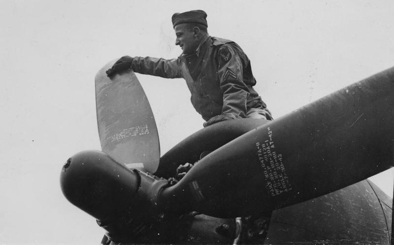 Corporal Robert Brud of the 303rd Bomb Group, cleans the propeller of a B-17 Flying Fortress. Passed for publication 16 Dec 1942. Printed caption on reverse: 'The Holidays He Missed. 23 year-old Robert Brud, of 4618 N. Melvina Avenue, is a corporal in the Air Corps. In private life he was with the Howard Radio Corporation of Belmont Avenue.