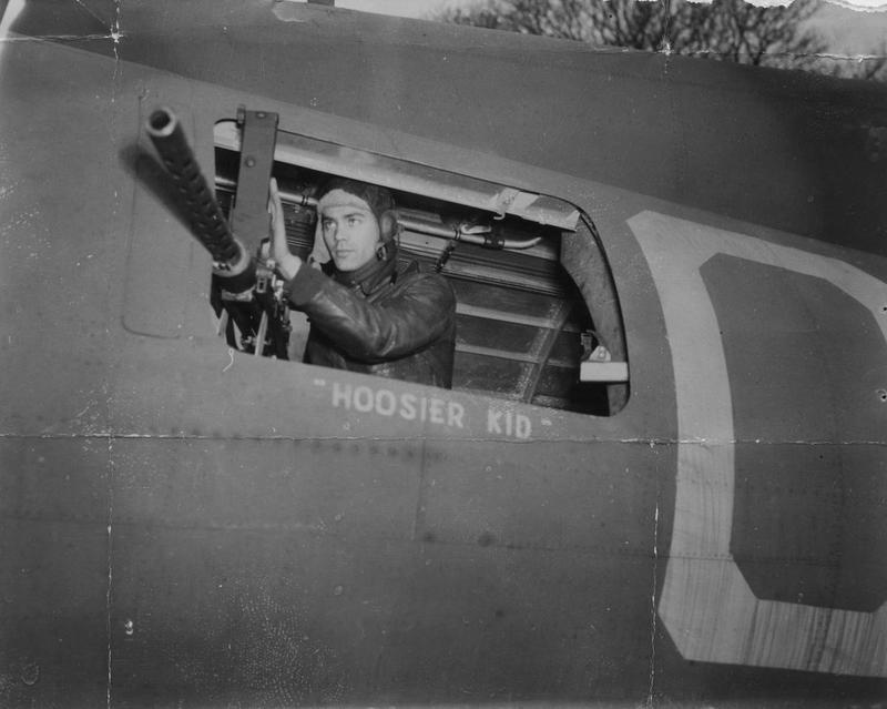 Staff Sergeant Richard C. Fortunak of the 303rd Bomb Group, checks his machine gun on his B-17 Flying Fortress. Passed for publication 25 Jan 1943. Printed caption on reverse: 'How The Boys Live And Work At Flying Fortress Station In England. Wide World Photo Shows:- Staff Sgt. Richard C. Fortunak, 1260 West 17th Avenue, Gary, Ind., Waist Gunner in a Fortress, which he and his crew mates have named