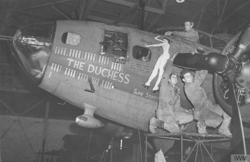 Ground crew work of the 303rd Bomb Group work on the engines of a B-17 Flying Fortress nicknamed