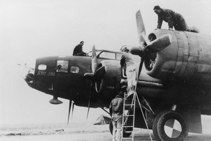 Ground crewmen of the 303rd Bomb Group work on the engines of a B-17 Flying Fortress nicknamed