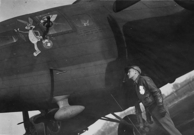 Captain Albert W. Dieffenback, a bombardier of the 303rd Bomb Group, admires Bugs Bunny painted onto the nose of his B-17 Flying Fortress. Passed as censored 9 May 1943. Printed caption on reverse: '14. Captain Albert W. Dieffenbach, of Garrett Park, Md., and the bomber in which he flies as group bombardier.' On reverse: US Army Press Censor ETO [Stamp].