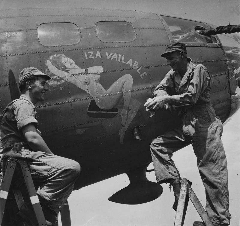 Two airmen of the 303rd Bomb Group admire the nose art of a B-17 Flying Fortress nicknamed