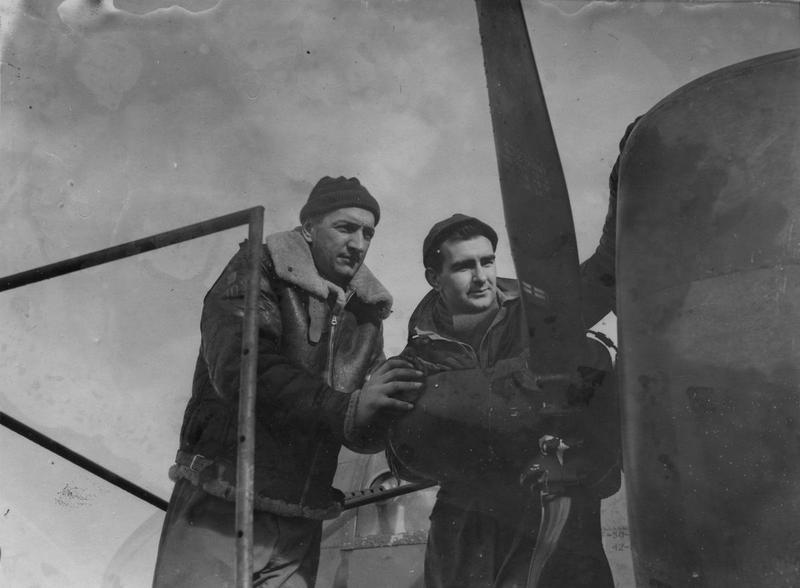 Master Sergeant Kazberovich and Master Sergeant Roy I. Ploeger of the 306th Bomb Group inspect the engine of a B-17 Flying Fortress. Passed for publication 2 Feb 1943. Printed caption on reverse: 'American Airmen Who Made First Daylight Raid On Germany. Associated Press Photo Shows:- The men responsible for the smooth running of the engines of the Fortress: Master Sgt. Kazberovich of Pittsfield, Mass. (left), and Master Sgt. Roy I Ploeger of Burley, Idaho. TET 254776. 1-2-43.' On reverse: Associated Press, US Army Press Censor ETO and US Army General Section Press & Censorship Bureau [Stamps].