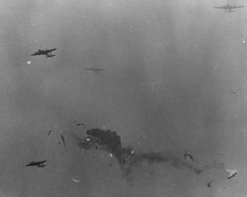 Two 305th Bomb Group B-17 Flying Fortresses collided in mid-air in heavy fog over Thurleigh airbase after returning from a mission; both were destroyed with all hands lost. Handwritten caption on reverse: '55819.' Printed caption on reverse: '55819 AC - Returning from a daylight bombing assault on important synthetic oil plants and key communications centers just behind von Rundstedt's lines, two B-17 Flying Fortresses collide in mid-air and disintegrate. None of the crews of either plane escaped. The fateful accident occurred only a few hundred feet off the ground as the formation roared through thick blanket of clouds that covered the base and reduced visibility to almost zero. The density of the overcast is indicated by the fact that only a few Fortresses of the formation, which numbered more than a score, are visible in this picture. This photograph is evidence of the weather hazards that U.S. Army 8th Air Force bomber crews are forced to brave almost daily during the winter months to continue without pause their sledge-hammer blows on industrial Germany and to provide tactical bombing cooperation for our ground forces. England. U.S. Air Force Photo.'