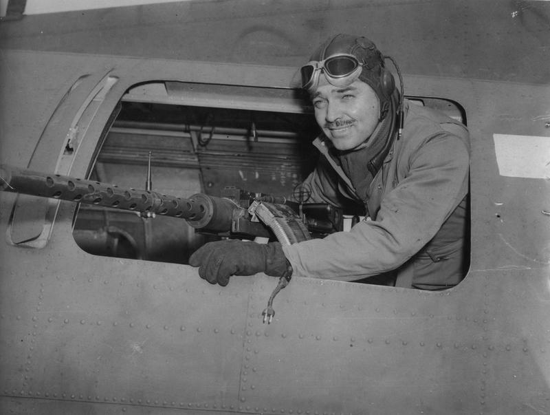 Hollywood actor Clark Gable in the waist gun position of a a B-17 Flying Fortress of the 91st Bomb Group. Passed for publication 6 Jun 1943. Printed caption on reverse: 'Clark Gable Serves In England: Clark Gable has slipped into this country as Capt. Gable and is serving with the U.S. Army Air Force somewhere in England, as a Gunnery Instructor. He hopes that his movements will not be accompanied by the publicity that he had a while ago, because he wants to get down to the job as others are doing. Keystone Photo Shows: Pictured in one of the centre gun turrets, Gable gives a smile for the cameraman.' On reverse: US Army Press & Censorship Bureau [Stamp]. 268124. [censor no.]