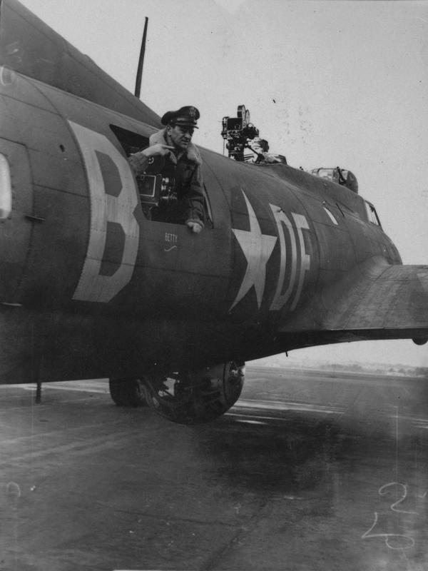 Film Director Major William Wyler looks through the waist gun position of a B-17 Flying Fortress (DF-B) of the 91st Bomb Group during the filming of 'Memphis Belle'. Passed as censored 1 Feb 1943. Printed caption on reverse: 'How a Flying Fortress Protects Itself: Major William Wyler, who directed the famous film 'Mrs Minniver', is now busy directing an instructional film for the U.S. Army Air Force, showing how a 'Flying Fortress' protects itself against attack by enemy fighters. The Fortress is loaded with cameras in place of the guns and Spitfires, piloted by U.S. Army Air Force Pilots, acting parr of enemy aircraft, are making the attacks, which are recorded by the cine-men and their cameras. Photo shows - Cameras installed on Fortress in place of guns.' On reverse: US Army Press & Censorship Bureau [Stamp]. Print No: 246348.