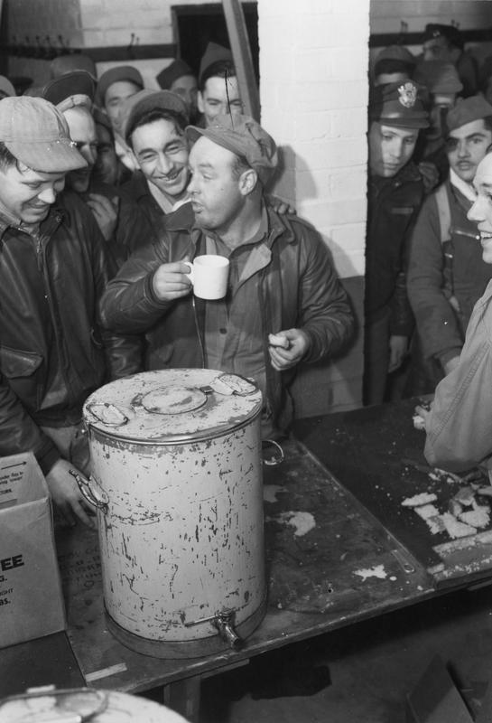 Technical Sergeant Edward Fee of the 91st Bomb Group enjoys a cup of coffee surrounded by his comrades at Bassingbourn after his final mission. Printed caption on reverse of print: 'A-27150 AC - HQ 8th AAF Photo Section, 20 Dec 1943. Ovation on Return. Congratulated on the completion of his tour of