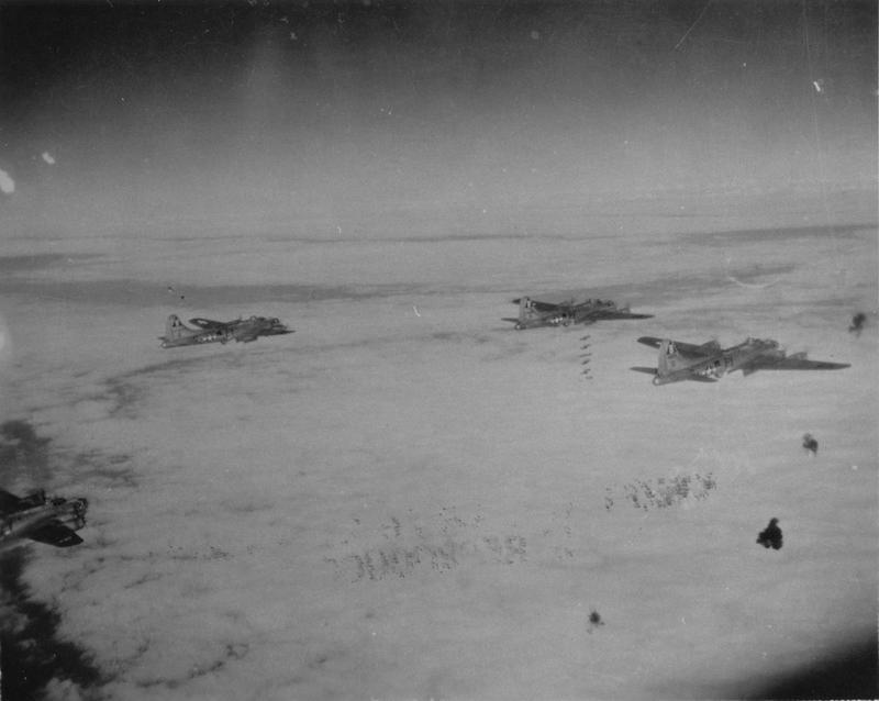 Three B-17 Flying Fortresses of the 407th Bomb Squadron, 92nd Bomb Group drop their bomb loads as flak bursts around them.