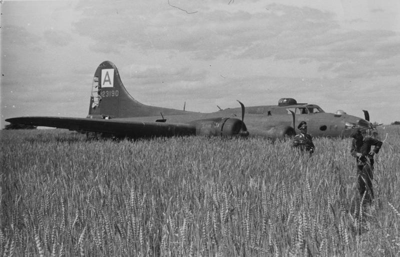 Two German soldiers guard the wreck of a crashed B-17 Flying Fortress of the 94th Bomb Group. Handwritten caption on reverse: '14/7/43.'