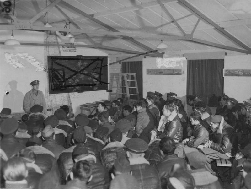 Colonel Fred Castle delivers a briefing to personnel of the 94th Bomb Group, December 1943.   A censor has obscured the maps and charts in the background. Image stamped on reverse: 'Associated Press'[stamp],'Passed for publication 14 December 1943.'[stamp] '296691.'[Censor no]    Printed caption on reverse: 'Operations Room at US Air Base. Preparing for take off. Associated Press photo shows: Col.F. W. Castle, Group Commanding Officer, gives the massed crews of the base the last part of the briefing, and a personal 'Godspeed' and 'Good Luck' in the briefing room before the start of the raid. Map that is covered in background has route map for raid but was covered for picture.'