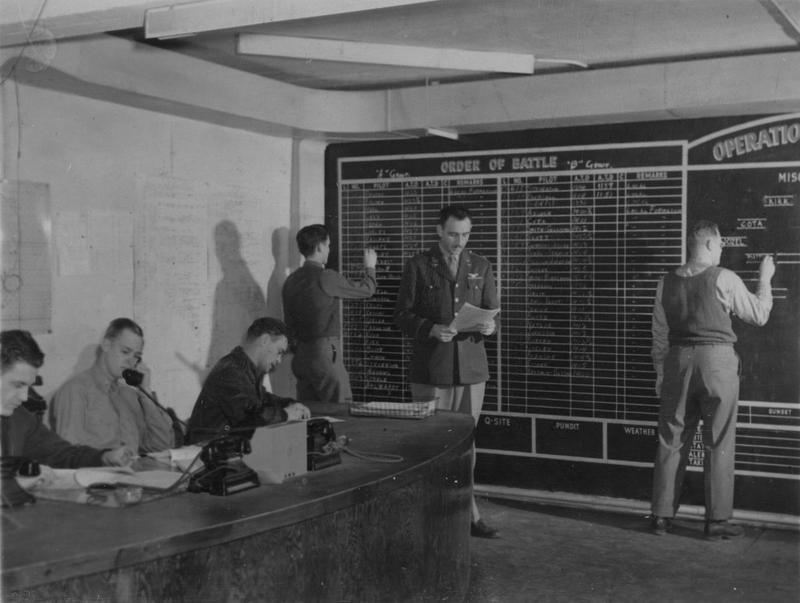 The operations room at Bury St Edmunds, December 1943  Handwritten caption on reverse: '94BG.' On reverse: Associated Press [Stamp], 'Passed for publication 14 December 1943.'[stamp].   Printed caption on reverse: 'Operations Room of US Bomber Base - Key spot and heart of the planning and organization of a mission is in the operations office of a base. Manned 24-hours a day, a funnel for all the incoming information and data that is needed to plan the thousands of details to complete a successful mission. The 'Ops' room is the brain of a bombing mission. Intelligence information about the target, planned bomb load, amount of gasoline needed to make the flight with a safe margin, are put together and readied to pass along the line to ground officers to put into effect , and to the crews at briefing before takeoff time. Associated Press photo shows: At work in the 'Ops Room' during the planning of a raid, left to right ; Assistant Operations Officer, Capt. James H. Ainsworth, Rutland, Ver, Lt. David B. Vinson Jr., 3110 Federal St., El Paso, Tex, Lt. Mathew Murray, 276 Great Kills Road, New York City, Sgt. M. D. Horn, 3822 NE Milton Portland, Ore, Col. Louis G. Thorup, Group Air Executive Officer, 115 Edith Ave., Salt Lake City, Utah, and S/Sgt. Joseph D. Lugosh Jr., 348 Springfield Terrace, Haddonfield, NJ.'
