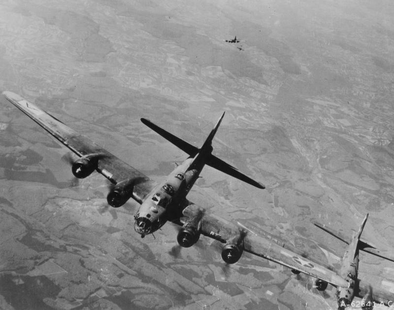 Three B-17 Flying Fortresses of the 94th Bomb Group are attacked by a Nazi Fighter aircraft during a mission. Printed caption on reverse of print: 'A-62641 USAF: Nazi fighter plane attacking Boeing B-17
