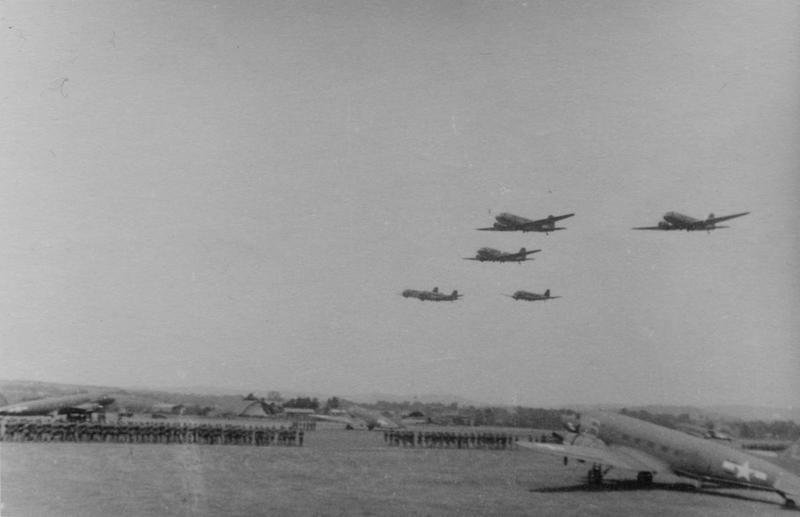 A formation of C-47 Skytrains of the 440th Troop Carrier Group fly over Exeter. Handwritten caption on reverse: 'Exeter: troops on parade.'