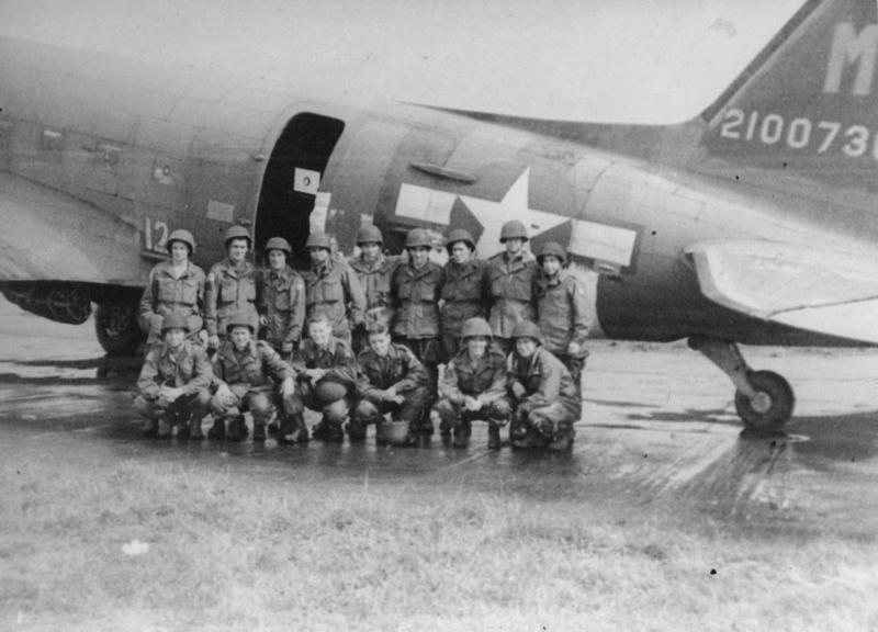 Paratroopers with a C-47 Skytrain of the 442nd Troop Carrier Group. Handwritten caption on reverse: 'Paratroopers before Holland mission. Fulbeck, England, Sept 1944. Ready for takeoff at runway.'