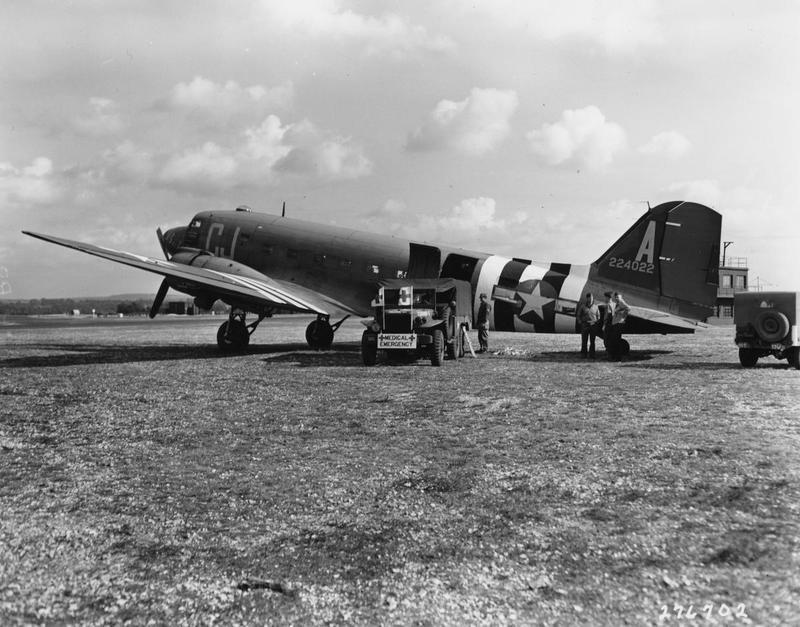 A C-47 Skytrain (CJ-A, serial number 42-24022) of the 71st Troop Carrier Squadron, 434th Troop Carrier Group is loaded with blood to be delivered to France. Handwritten caption on reverse: 'SC 276702. Believed Aldermaston, but could be Greenham.' Printed caption on reverse: 'Dava Still Media Depository, Bldg. 168, N.D.W., Washington, D.C., 20374. SDAN: SC 276702. Date: 06/12/44. Savrin: Service ID: ETO-SOS-44-599. Photographer: Holt. England...At a landing field in England, a critical cargo of whole blood, to be given to battle casualties, is loaded on a C-47 transport plane, France bound, U.S. Army. blb. Official U.S. Army Photo (Released).' On reverse: National Archives [Stamp], credit number 111-SC-276702.
