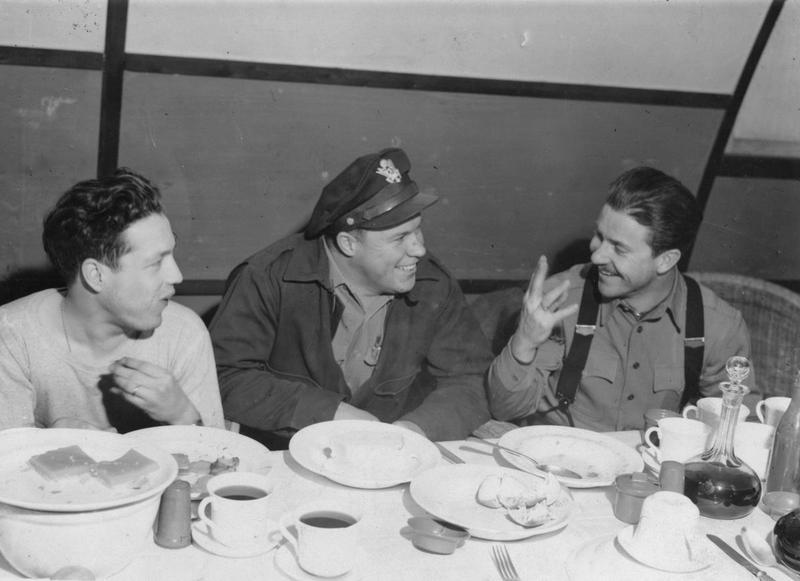 Lieutenant Lester A. Gibson, Colonel Maurice A. Preston and Major Otis E Parks of the 379th Bomb Group enjoy a meal after returning from a mission.  Handwritten caption on reverse: '47.'. Censor no: 298752. On reverse: Associated Press [Stamp].   Printed caption on reverse: 'THE LEADERS TALK IT OVER. Associated Press Photo Shows: The leaders of yesterday's ( January 4) raid on Germany - Berlin Radio said that Kiel was the target - Exchange experiences as they enjoy a hot meal on their return. They are (Left to Right): Lt Lester A. Gibson, tailgunner and observer in lead plane over the target, of 8214 Tumet St., Detroit, Mich; Col. Maurice A. Preston, Pilot and C.O. of the lead ship of the combat wing, of Tulare, Calif., and Major Otis E. Parks, of 1225 Clifton Road N.E., Atlanta, Georgia, who led the low group of the combat wing which was first over the target. Col. Preston Flew the ship,