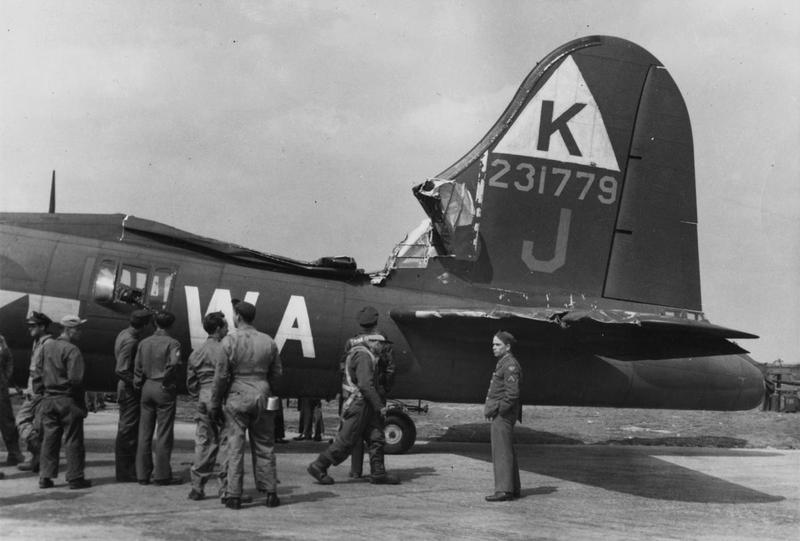 Ground personnel of the 379th Bomb Group inspect a damaged B-17 Flying Fortress (WA-J, serial number 42-31779) after a mission, 24 May 1944. Printed caption on reverse: '71356 AC - Members of the 379th Bomb Group inspect a Boeing B-17
