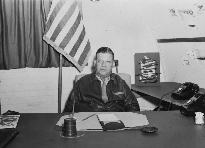 Colonel Lester J Maitland, commanding officer of the 386th Bomb Group, in his office. A censor has obscured the insignia behind him. Passed as censored 30 Sep 1943. Handwritten caption on reverse: 'At Boxted, Aug 1943. Col L.J. Maitland.' Printed caption on reverse: 'AMERICA'S