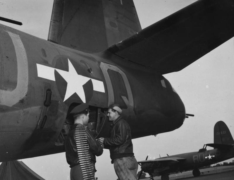 Technical Sergeant John P. Spottiswoode and Staff Sergeant Joseph R. Pakulski of the 386th Bomb Group load ammunition into the waist guns of their B-26 Marauder (RU-Q, serial number 41-34971) nicknamed