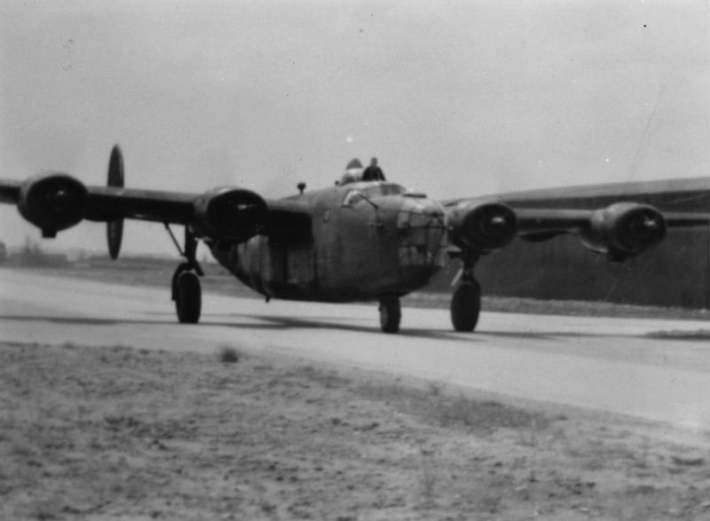A B-24D Liberator 'Carpetbagger' - extensively modified for specialised operations - taxiis on the perimeter track at Harrington airfield. Printed caption on reverse: 'A Carpetbagger B-24D taxiing on the perimeter at Harrington. Photo -