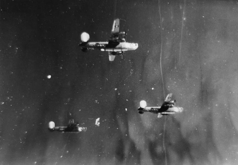 Three 844th Bomb Squadron, 489th Bomb Group B-24 Liberators fly in formation above the photographer's aircraft. The aircraft are: top-centre,