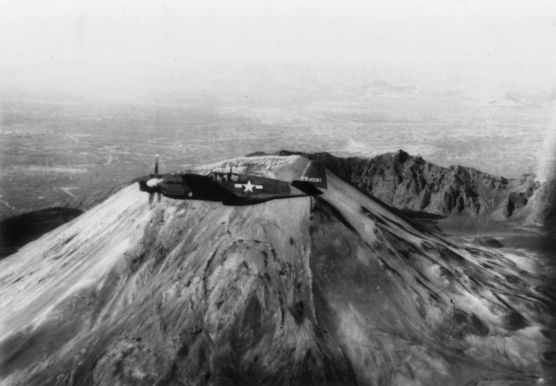 An A-36 Mustang (serial number 42-84081) of the 27th Fighter Bomber Group, 12th Air Force in flight over Mount Vesuvius. Handwritten caption on reverse: '42-84081 A-38A over Vesuvius.'