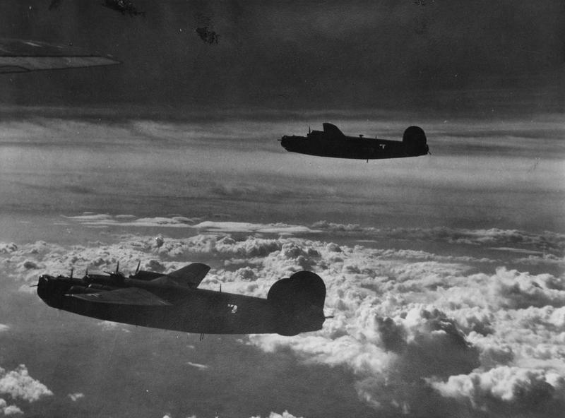 Two B-24 Liberators of the 460th Bomb Group, 15th Air Force fly together during a mission. Handwritten caption on reverse: '15 AF B-24s 460th BG.'