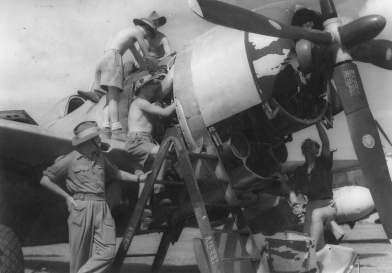 RAF ground personnel service the engine of a P-47 Thunderbolt in Batavia, 1945. Printed caption on reverse: 'BRITISH OFFICIAL PHOTOGRAPH (AIR MINISTRY) CROWN COPYRIGHT RESERVED. RAF IN BATAVIA. RAF ground crews at Kemajoran airfield in Batavia service Thunderbolt aircraft in readiness for operations against the Indonesians in Sourabaya. CF 843. Left to right- Sergeant A Dennison of 12, Parkmount Garden, Thore Road, Belfast; Leading Aircraftman T Heron of Monkstown, Co. Antrim; Leading Aircraftman W. McCleave of 34 Bootle Street, Belfast; Leading Aircraftman Caffrey of 32 Mount Street, Dublin; and Flgith Sergeant A McGrath of Millbrook Road, Lisburn, Ireland. Picture issued 1945.'