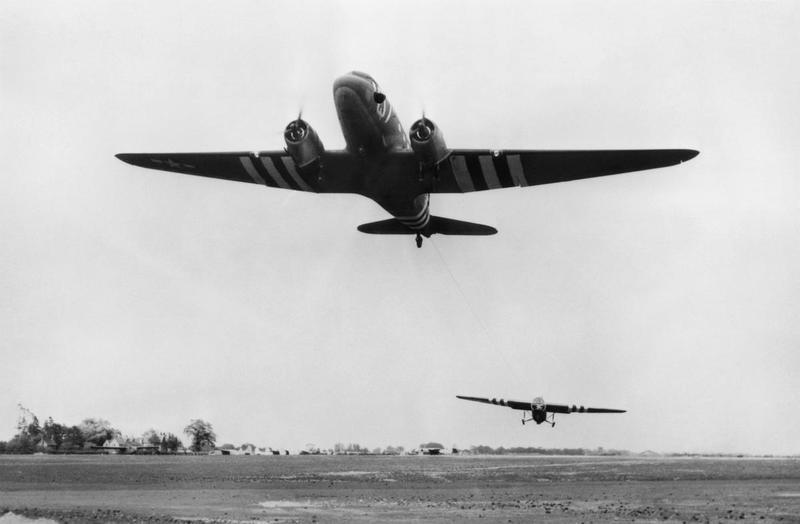 A C-47 Skytrain of the 438th Troop Carrier Group tugs a glider, as it takes off from Greenham Common on D-Day. Handwritten caption on reverse: '438 TCG. Greenham Common, 6/6/44.'