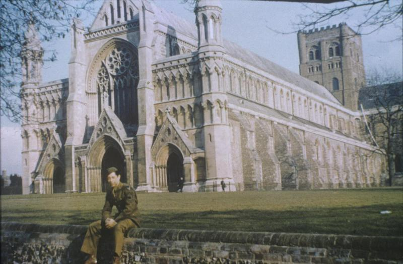 Technical Sergeant Roger Fraleigh of the 55th Fighter Group at St Albans Cathedral. Image by Robert Sand, 55th Fighter Group. Written on slide casing: 'Roger Fraleigh, St Albans Cathedral 1944.' Caption from Sand's file. Slide 4-64