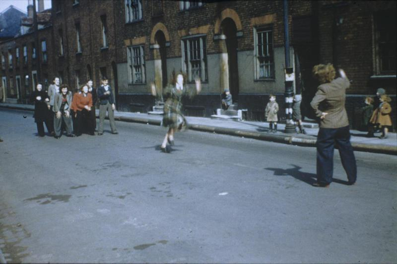 Girls dancing in the street in Harwich. Image by Robert Sand, 55th Fighter Group. Written on slide casing: (Harich)- Harwich, 30/3/45'  Associated caption: 'Bunch of Kids skipping rope on a street in Hawich. Boy! I wished I could enter in the fun, but my rope skipping days were too far in the past. The kid's didn't acknowledge that I was there, even when I took this picture. From here, bicycled to Clacton on Sea. Stayed overnight at a small hotel or lodging house, March 30 1945.'