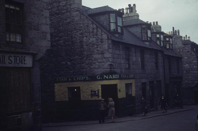 Nardi's fish and chip shop in Aberdeen, photographed by an airman of the US Army Air Forces in 1944. The shop was at 181 Gallowgate, just before the turning off to Spring Garden. There is a sign to a nearby shelter on one of its walls.   Written on slide casing: 'Aberdeen, 1944.'