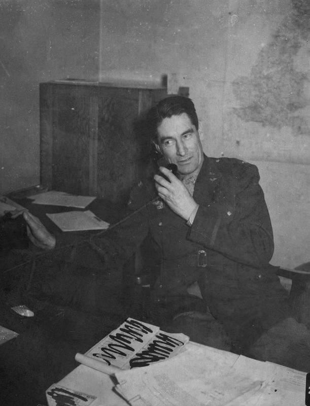 Colonel Bartlett Beaman at work at his desk. A censor has obscured the documents on his desk. Image stamped on reverse: 'Wide World.' [stamp], 'Passed for publication 2 Feb 1943.' [stamp]. Printed caption on reverse: 'BEHIND-SCENES PICTURES OF US ARMY AIR FORCE HEADQUARTERS WING IN ENGLAND. This set of Wide World pictures was made recently in England and shows behind-the-scenes glimpses of the work and life of a Headquarters wing of the US Army Air Force. Headquarters wing is supply section and coordination centre of operational data for the Squadron it serves. The men working in