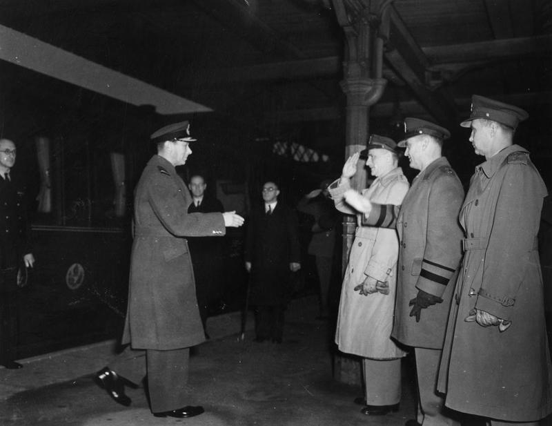 King George VI meets Major General Carl Spaatz, Major General Ira Eaker and General Newton Longfellow at Huntingdon. Image stamped on reverse: 'Unofficially Approved.' [stamp], 'Confidential.' [stamp], 'Passed for publication 14 Nov 1942.' [stamp] and '233091.' [Censor no.] Printed caption on reverse: 'ET-HQ-42-1548, Nov 14-42. For purpose of first visit to US Bomber forces somewhere in Engl., His Majesty King George VI is met (l to r) by Major Gen Carl A Spaatz, CGUS Bomber Com, ETo, Major Gen Ira Eaker, Com. of Bomber Com. And Brig Gen Newton Longfellow. Huntingdon Station, Huntingdon, Engl [obscured by censor].'