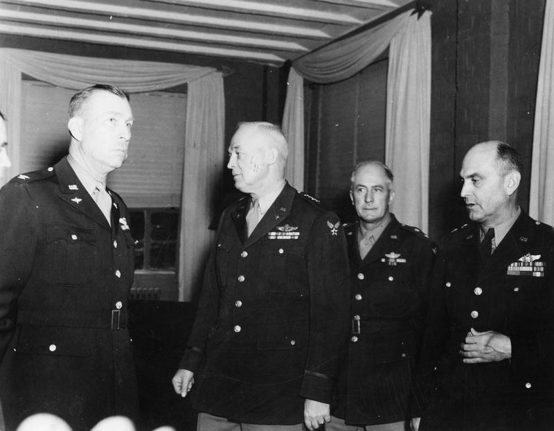 Colonel Neal Creighton, General H.H. Arnold, Major General Henry J.F. Miller, and General Ira C. Eaker. Image stamped on reverse: 'Passed for publication 3 Sept 1943.' [stamp], '34579.' [censor no.] Printed caption on reverse: 'US ARMY AIR FORCES OFFICIAL PHOTO. From left to right: Colonel Nel Creighton, of Chapel Hill, NC, Post Commander of Camp Griffiss, General H H Arnold, Major General Henry JF Miller, Commanding General of VIII Air Force Service Command, and General Ira C Eaker, commanding General of Eighth Air Force. This is one of the first pictures to be taken of Gen Arnold on his arrival in England for conferences.'