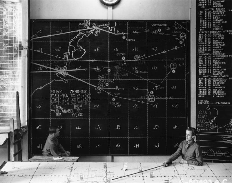 The operations room of the 65th Fighter Wing at Saffron-Walden. Printed caption on reverse: '60493 AC- Plotting table in the operations room of the 65th Fighter Wing, Saffron-Walden, Essex, England. US Air Force photo.'