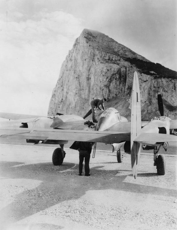 Airmen of the 14th Fighter Group, 12th Air Force work on a P-38 Lightning in Gibraltar. Image stamped on reverse: 'Not to be published 26 Nov 1942'[stamp], '235287.'[censor no.] Printed caption on reverse: 'AFNA-ZEI-42-1745, Nov 10 42. US fighter plane on air-drome somewhere in Mediterranian theater of war'
