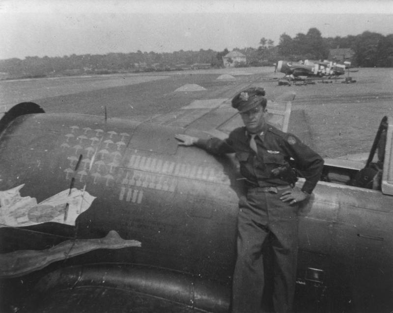 Lieutenant Julian Morford of the 405th Fighter Group on the wing of his P-47 Thunderbolt. Printed caption on reverse: 'Lt Julian Morford, 511th FS, with his razorback at Christchurch shortly after D-Day. Note invasion stripes on aircraft in background.' Handwriten caption on reverse: 'Julian Morford, 511 FS, ALG 416 Christchurch Eng.'