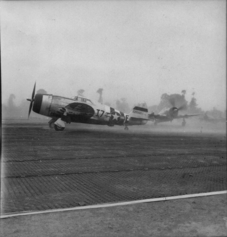P-47 Thunderbolts of the 48th Fighter Group line up for take off in Normandy. Image stamped on reverse: 'Associated Press.' [stamp], 'Passed for publication 19 Jun 1944.' [stamp] an d'330049.' [Censor no.] Printed caption on reverse: 'P-47S GO INTO ACTION IN NORMANDY. Associated Press Photo shows: From one of the newest airstrips built in France to accomodate the heavy American Thunderbolts. P-47s Fighter Bombser refuelled and re-armed taxi to the starting line in clouds of dust for another trip in their hunt for Germans to be straffed.'