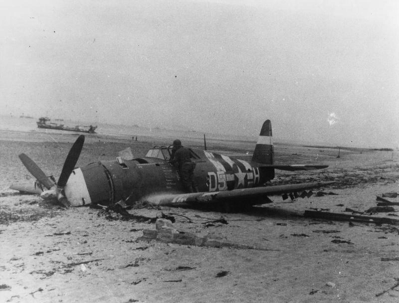P-47 Thunderbolt (D5-H, serial number 42-76297) of the 365th Fighter Group that has crash landed on a beach. Handwritten caption on reverse: 'Serial 276297 D5-H.'