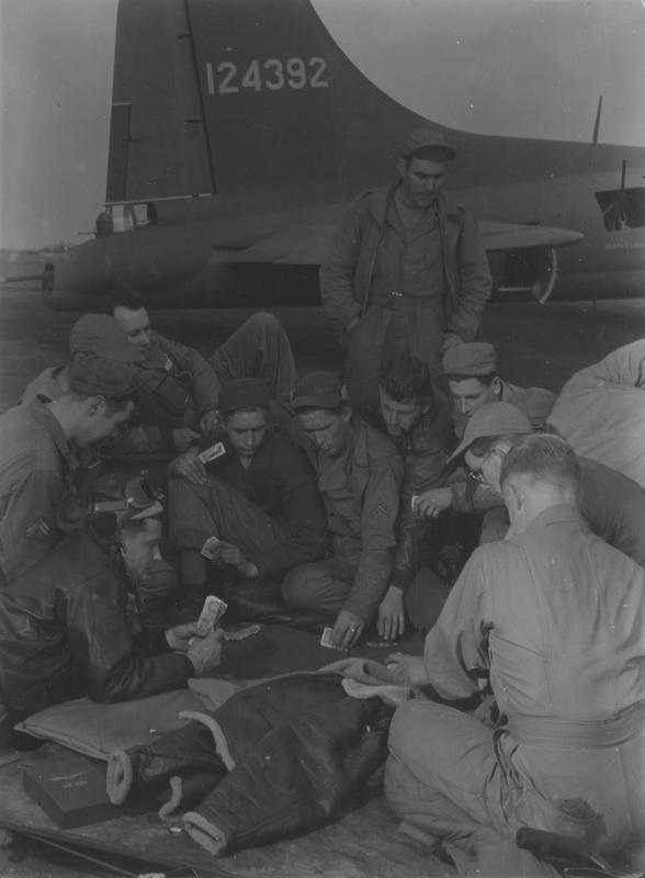 The crew of a 97th Bomb Group B-17 Flying Fortress (serial number 41-24392) play poker near the tail of their aircraft. Printed caption on reverse: 'Fortress crews play poker near their planes.' On reverse: Life Magazine Photo [Stamp].