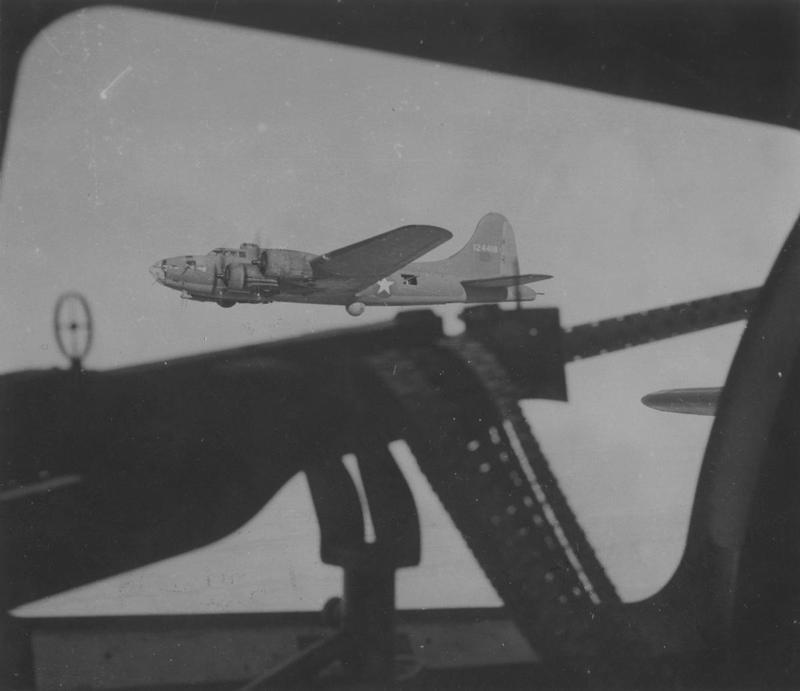 Wes Gallagher, a war correspondent for the Associated Press stationed in North Africa, was allowed aboard a 301st Bomb Group B-17 Flying Fortress on the Group's raid on Tunis in early January 1943. He photographed one of the 301st Bomb Group B-17 Flying Fortresses (serial number 41-24418) through the waist gunner's window aboard the B-17 Flying Fortress he was riding in. Passed for publication 16 Jan 1943. Handwritten caption on reverse: '301BG.' Printed caption on reverse: 'Pictures Taken During Actual Bombing Raid On Tunis When 19 German Fighters Were Shot Down. This interesting series of photographs were taken by Wes Gallagher, the Associated Press War Correspondent in North Africa, when he flew in one of the bombers which raided Tunis at the beginning of this year. Flying Fortresses carried out the raid, escorted by P-38 fighters. The sortie resulted in the biggest air battle on the Tunisian front to date, 19 German fighters being shot down. Associated Press Photo Shows:- The Fortresses start lining up wing to wing for the attack. This is how one of the bombers looked from the waist gunner's position in the photographer's plane. GAP 254302. 16-1-1943.' Censor no: 243403. On reverse: Associated Press, US Army Press Censor ETO and US Army General Section Press & Censorship Bureau [Stamps].