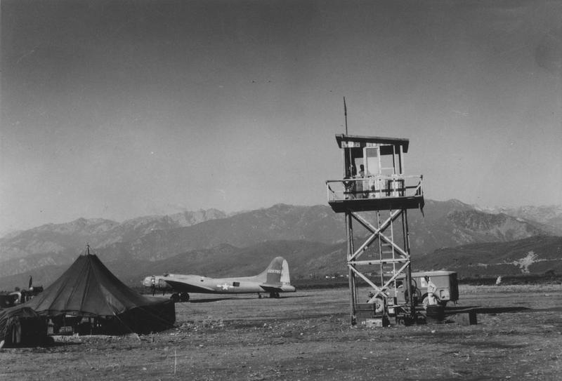 A B-17 Flying Fortress (serial number 42-29790) parked by the control tower of the 94th Fighter Squadron, 1st Fighter Group's airbase in Corsica. Handwritten caption on reverse: 'B-17.' Printed caption on reverse: '75657 AC - Control tower of the 94th Fighter Squadron, 1st Fighter Group in Corsica. U.S. Air Force Photo.'