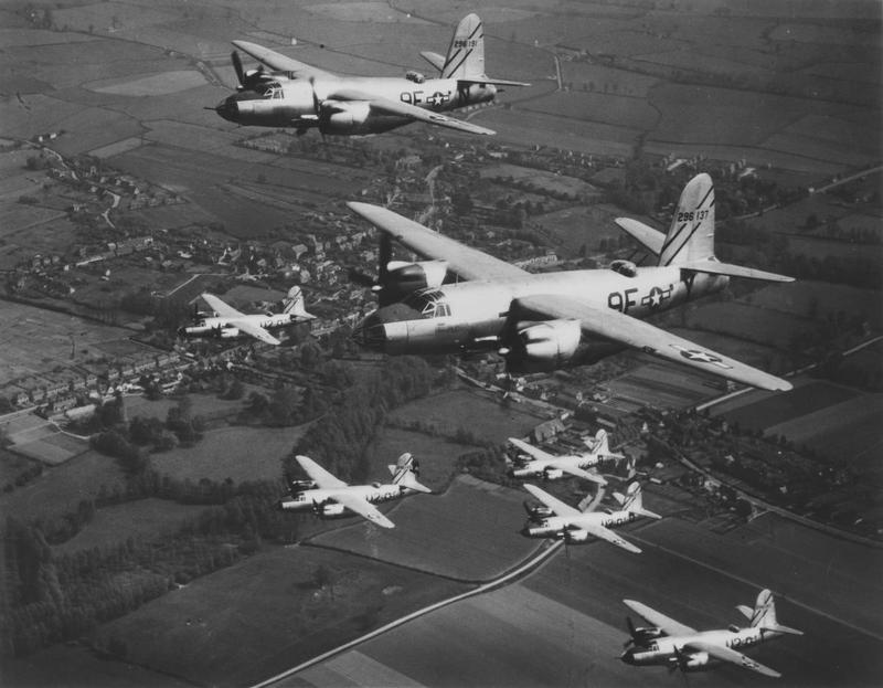 B-26 Marauders of the 597th Bomb Squadron ('9F') and the 598th Bomb Squadron ('U2'), 397th Bomb Group, fly towards Europe on a raid. The lower flight are all 598th Bomb Squadron aircraft; the two upper B-26 Marauders (9F-Y, serial number 42-96137 in front; 9F-N, serial number 42-96191 behind) are 597th Bomb Squadron aircraft. Handwritten caption on reverse: '597 BS (9F) & 598 BS (U2) of 397BG.' Printed caption on reverse: '52421 USAF - A Ninth Air Force Bomber Base, England - Silver Streak Marauders Over England's Famed Countryside. Here, in formation, are the