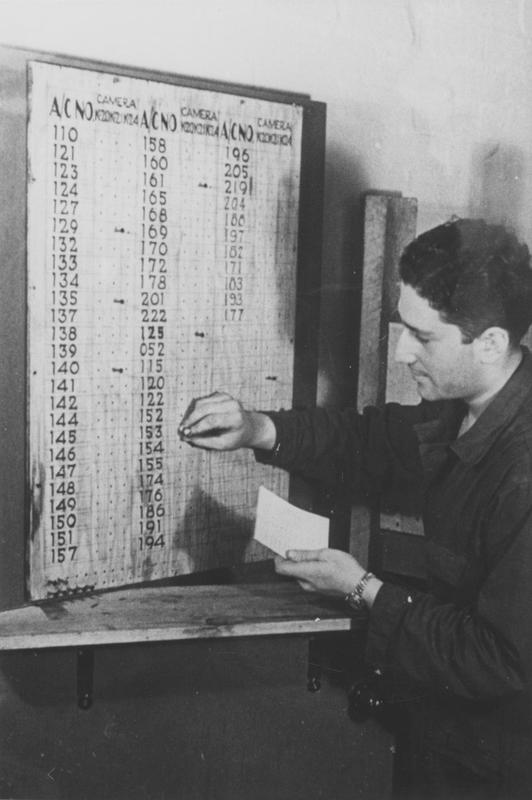 The operations board of the 397th Bomb Group, based at Rivenhall airfield, is updated by a crewman. The board shows the last three numbers of the squadrons' aircraft's serial numbers. Handwritten caption on reverse: 'Operation Board, 397 BG; Last three serial; Rivenhall; (Image) Col. James Snow via K. Fisher.'